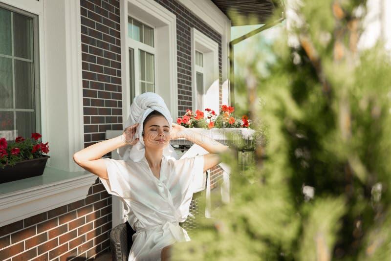 Robe de chambre de port de belle jeune femme heureuse de brune et serviette blanche stratching après sommeil sur la terrasse image stock