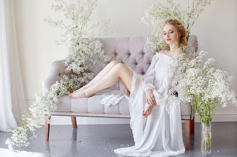 Robe de lumière blanche de fille et cheveux bouclés, portrait de femme avec des fleurs à la maison près de la fenêtre, pureté et  photographie stock