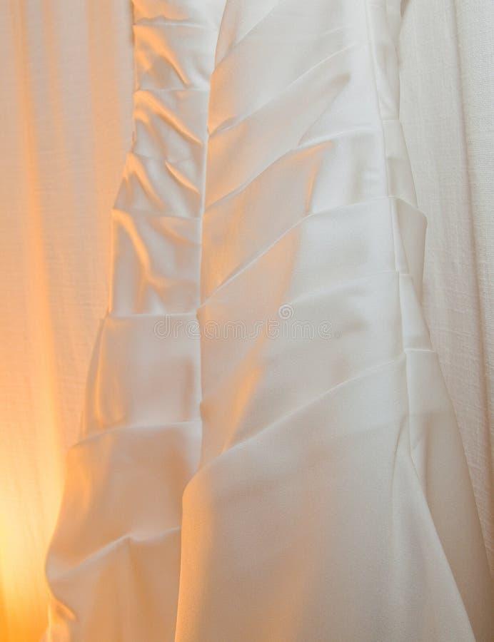 Robe de mariage blanche accrochant avec la lumière jaune molle photo libre de droits