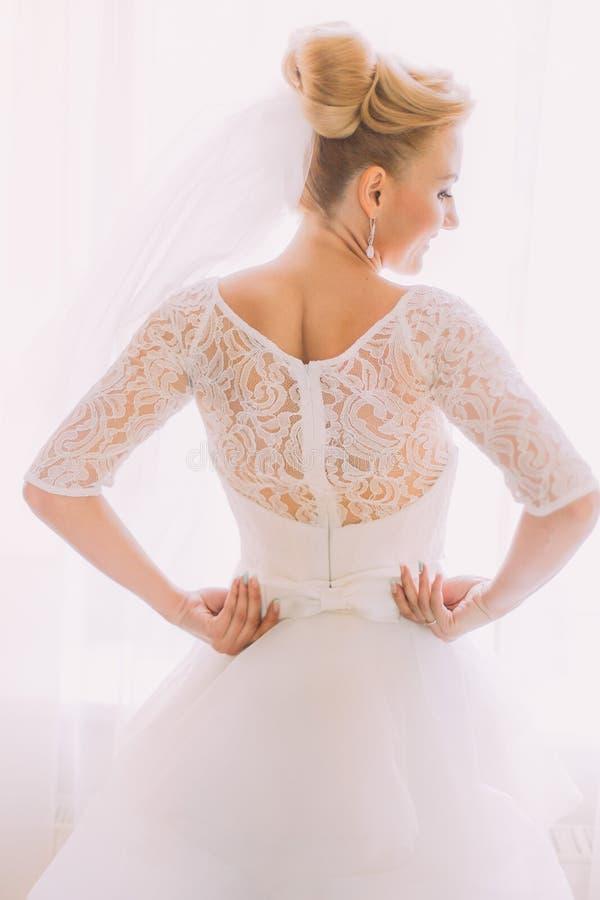 Robe de mariage blanche de vintage élégant élégant avec des ornements sur le plan rapproché arrière de la jeune mariée photo libre de droits