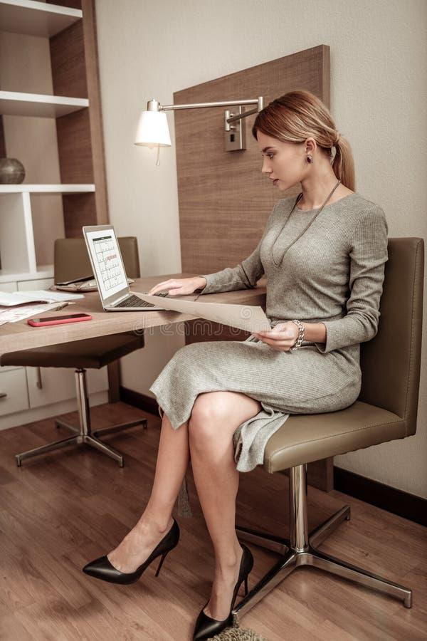 robe de port et accessoires de femme aux cheveux blonds travaillant sur l'ordinateur portable image libre de droits