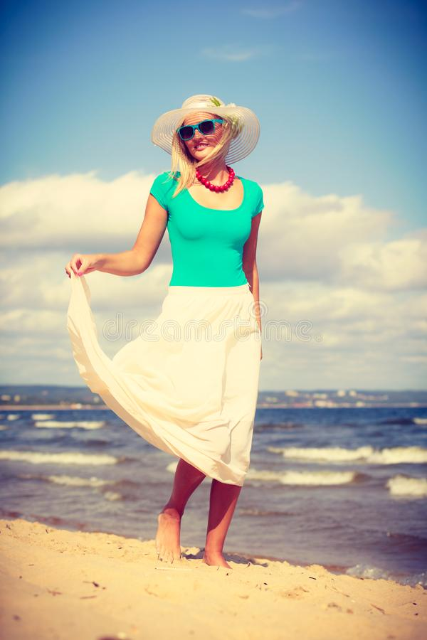 Robe de port de femme blonde marchant sur la plage photographie stock