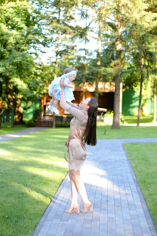 Robe de port de jeune femme de brune tenant peu de bébé dans le jardin photographie stock