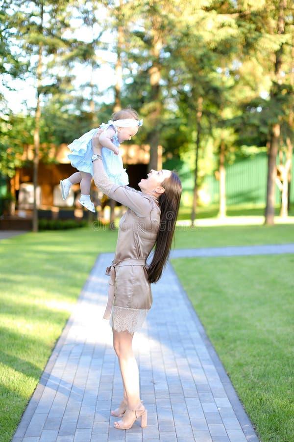 Robe de port de jeune femme heureuse tenant peu de bébé dans le jardin image libre de droits