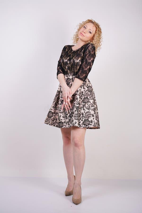 Robe de port de ville de dentelle de jolie femme adulte blonde et pose sur le fond blanc d'isolement fille de mode dans l'e court images stock
