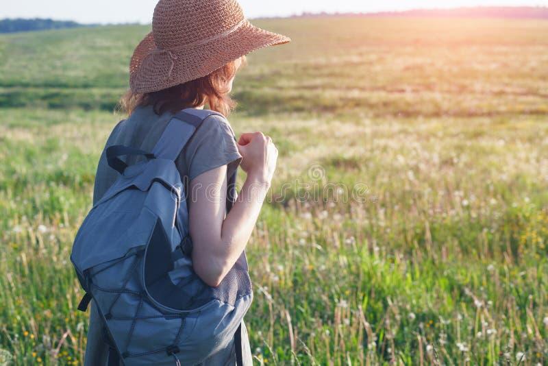Robe et chapeau de paille de toile de port de femme avec le sac à dos prêt à voyager et à explorer de nouveaux endroits et pays photos stock