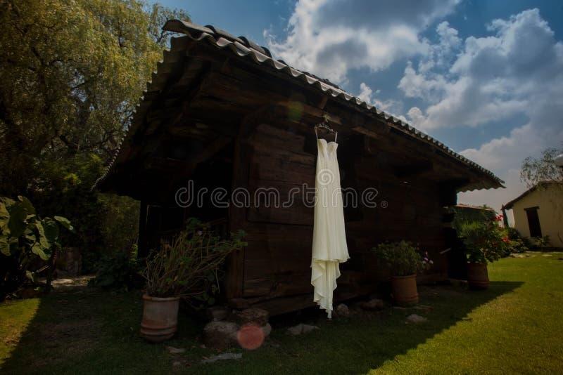 Robe l'épousant blanche de luxe de jeune mariée pendant de la cabine en bois au lieu de rendez-vous mexicain de Hacienda photos libres de droits