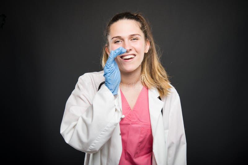 Robe longue de port de jeune portrait de docteur faisant hurler le geste photographie stock