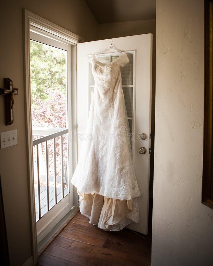 Robe nuptiale accrochant sur la porte photographie stock libre de droits