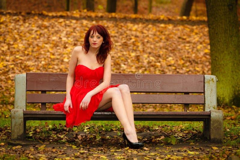 Robe rouge de femme se reposant sur le banc en parc d'automne image stock