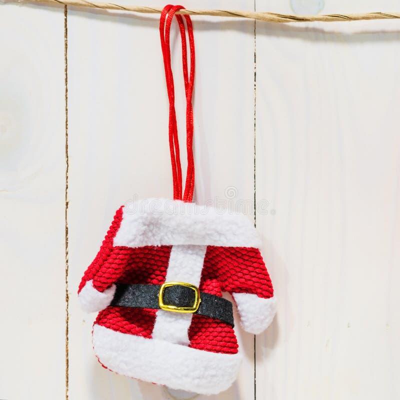 Robe rouge de Santa accrochant sur le mur en bois image stock