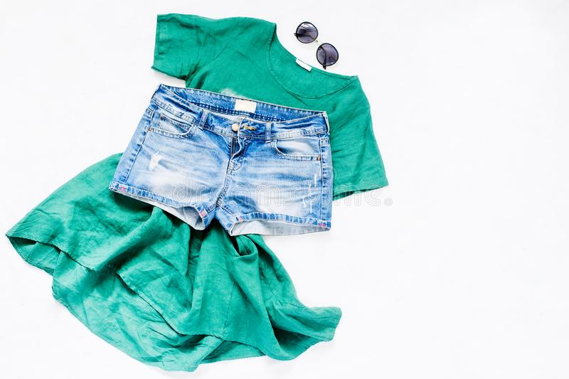 Robe verte, shorts de denim et lunettes de soleil sur le fond blanc image libre de droits