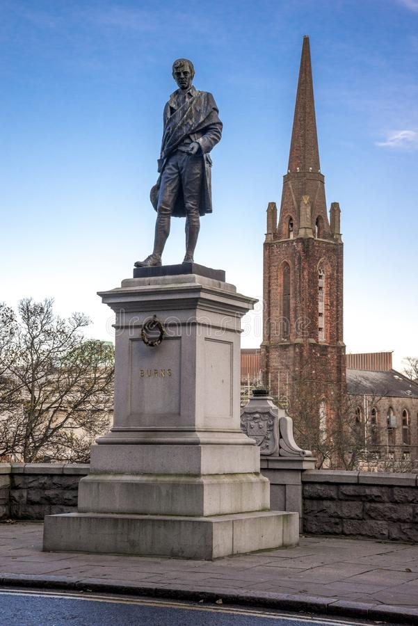 Robert Burns statue near Union Terrace Gardens and gothic style tower on background, Aberdeen, Scotland royalty free stock photos
