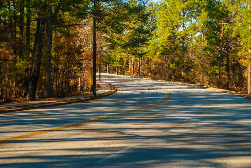 Robert E Lee Boulevard in Stone Mountain Park, Georgia, USA. The turn of the Robert E Lee Boulevard with long shadows of trees in the Stone Mountain Park in royalty free stock photos