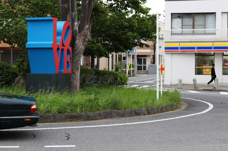 A Robert Indiana `Love` sculpture on a small traffic roundabout in Chiba City. royalty free stock images