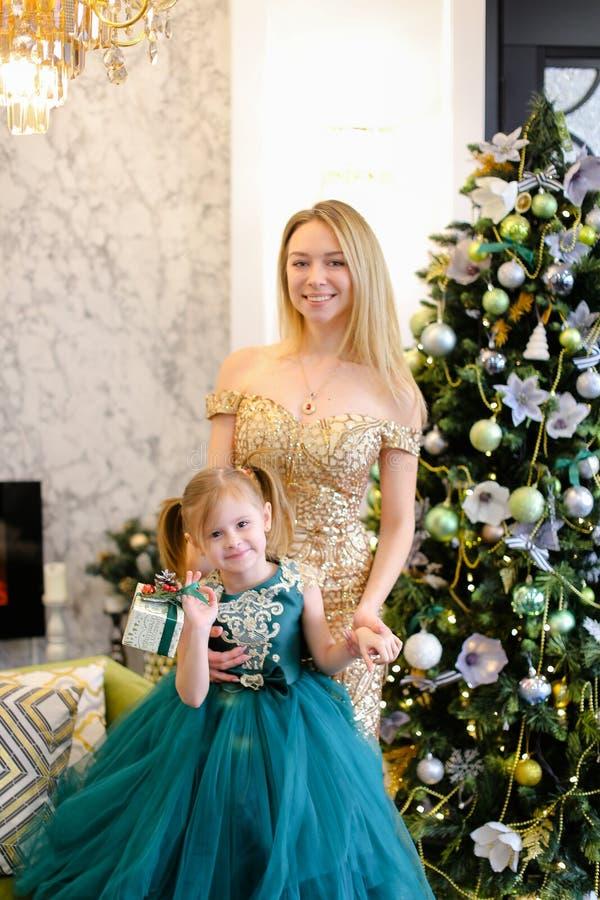 Robes de port de jeune mère et de petite fille tenant l'arbre de Noël proche images libres de droits