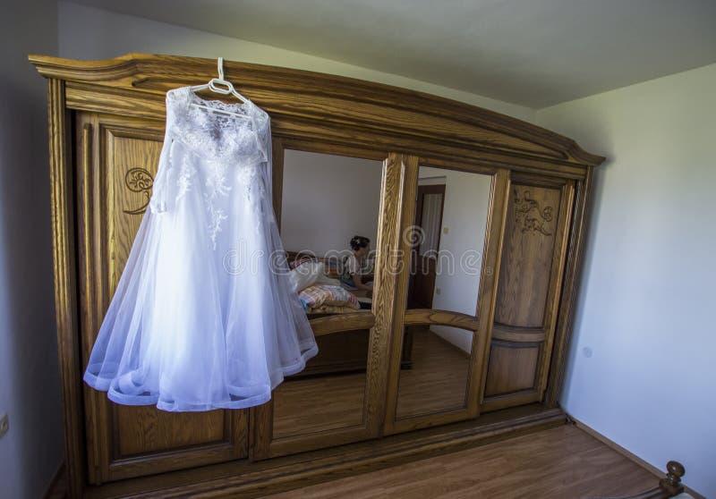 Robes les épousant blanches d'une jeune mariée accrochant sur une vieille garde-robe en bois avec des miroirs photo stock