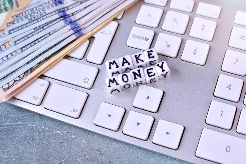 Robić pieniądze onlinemu pojęciu z komputerową klawiaturą, dolarowymi rachunkami i sześcianami z tekstem, fotografia stock