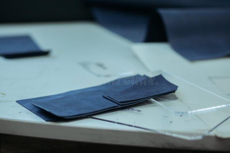 Robić rzemiennym portflom na szwalnej maszynie rzemieślnikiem na białym stole W pobliżu jest kilka konfekcyjna skóra obrazy stock
