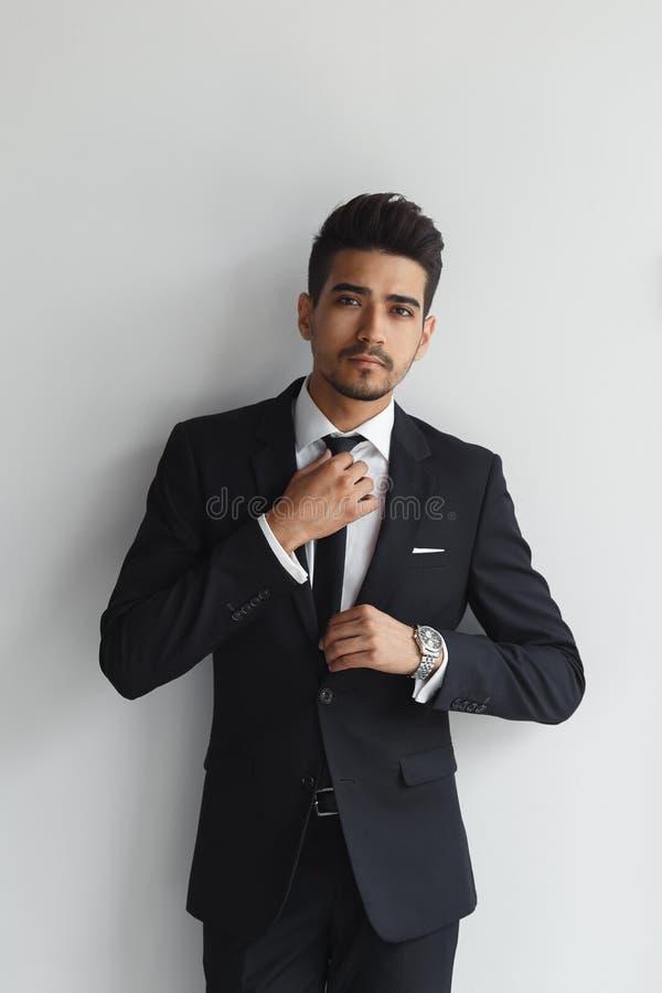 Robić biznesowemu spojrzeniu dobry Ufny młody człowiek przystosowywa jego krawat i patrzeje kamerę w formalnej odzieży podczas gd fotografia stock