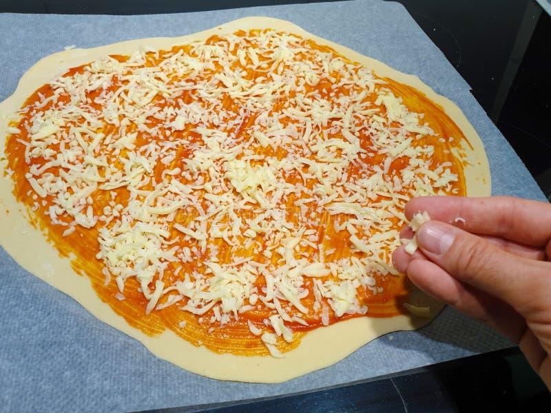 Robić domowej roboty pizzy w domu Ty możesz widzieć ciasto z pomidorem już przedłużyć i teraz dodaje kraciastego ser obrazy royalty free