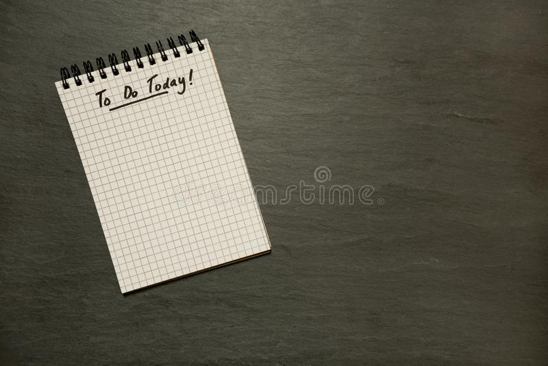 Robić dzisiaj spisuje na gridded ślimakowatym notepad naglącym - na zmroku łupku zdjęcie stock