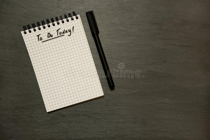 Robić dzisiaj spisuje na gridded ślimakowatym notepad z piórem, naglącym - na zmroku łupku zdjęcia stock