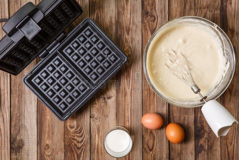 Robić gofrom mleko i jajka w domu - gofra żelazo, ciasto naleśnikowe w pucharze i składniki, - zdjęcie royalty free