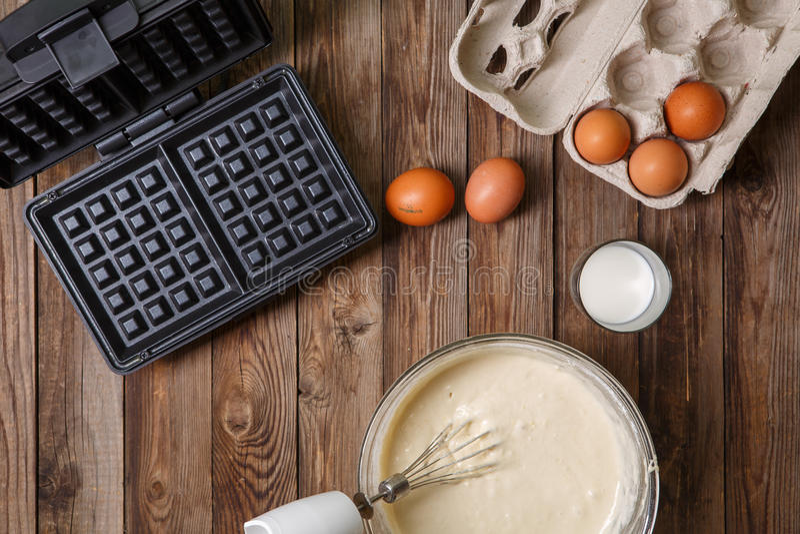 Robić gofrom mleko i jajka w domu - gofra żelazo, ciasto naleśnikowe w pucharze i składniki, - fotografia royalty free