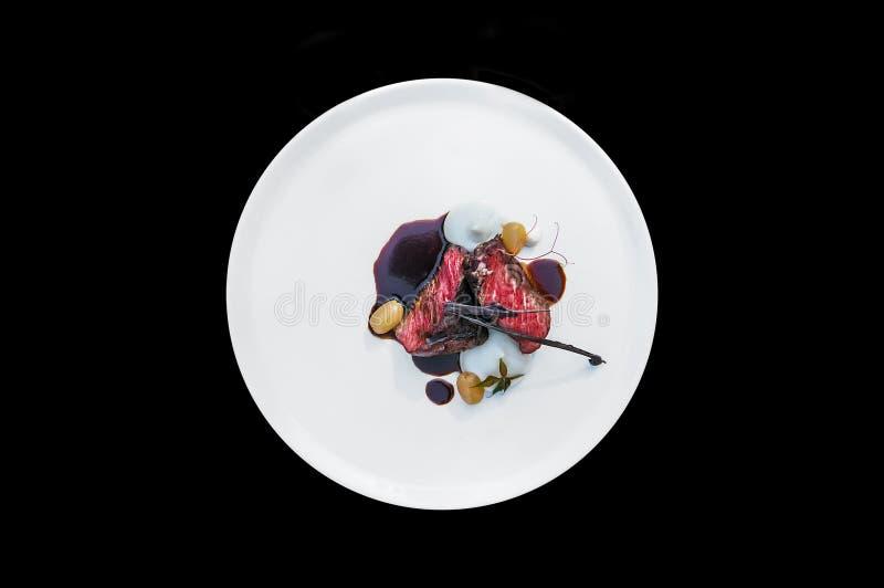 Robić kawałek mięso na talerzu odizolowywającym na czarnym tle obrazy royalty free