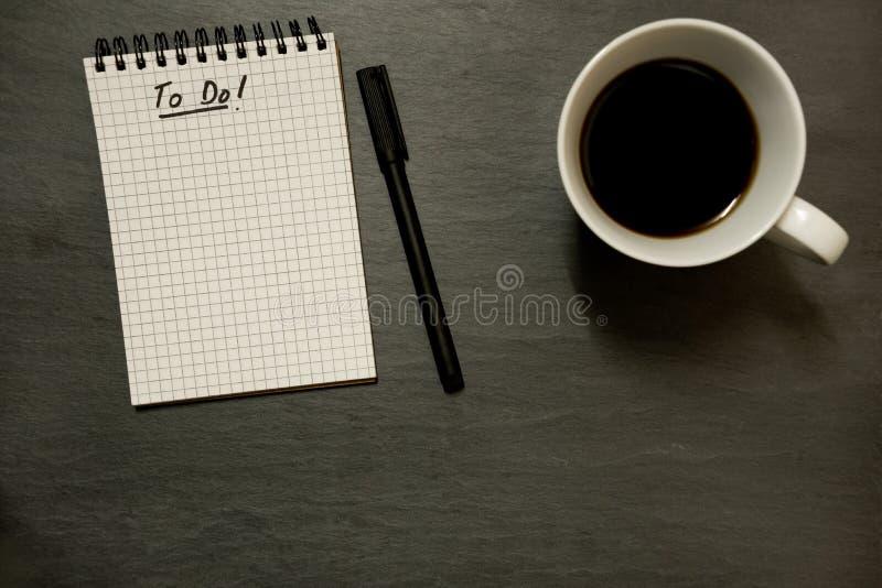 Robić liście na gridded ślimakowatym notepad z filiżanką kawy, na łupkowym stołowym wierzchołku od above -, minimalny zdjęcie royalty free