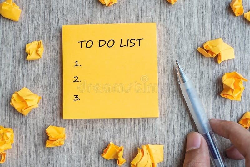 ROBIĆ listy słowu na kolor żółty notatce z biznesmena mienia piórem i rozdrobniącym papierze na drewnianym stołowym tle Biznesowi obrazy royalty free