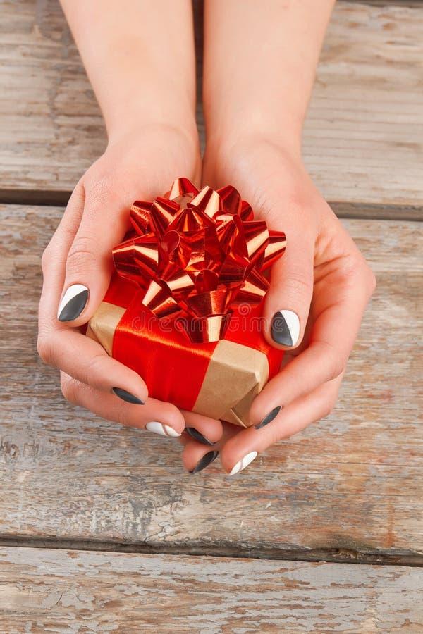 Robić manikiur ręki trzyma małego prezenta pudełko zdjęcie royalty free