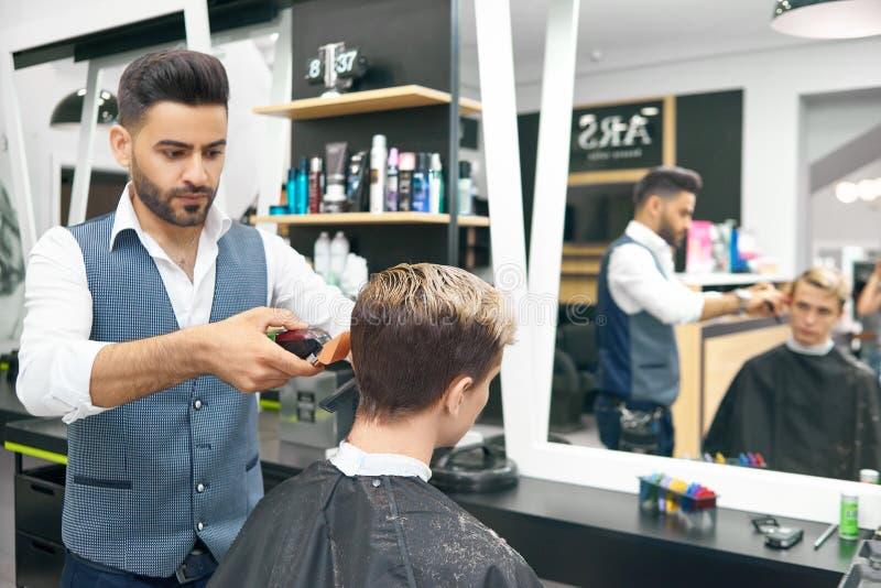 Robić nowej nowożytnej fryzurze dla młodego człowieka w fryzjera męskiego sklepie obraz royalty free