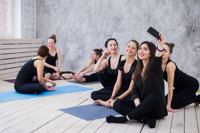 Robić selfie Grupa dziewczyny w sprawności fizycznej klasie patrzeje telefon komórkowego przy przerwą, szczęśliwy i uśmiechnięty, obrazy stock