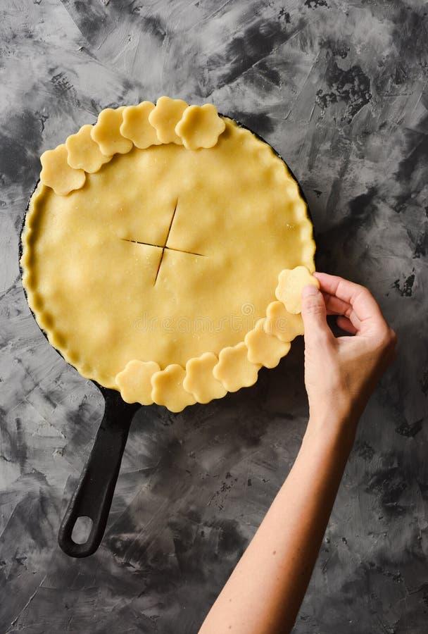 Robić tradycyjnemu jagodowemu kulebiakowi w obsadzie odprasowywa nieckę Nikła kobiety ręka dekoruje skorupę surowy kulebiak przed fotografia royalty free