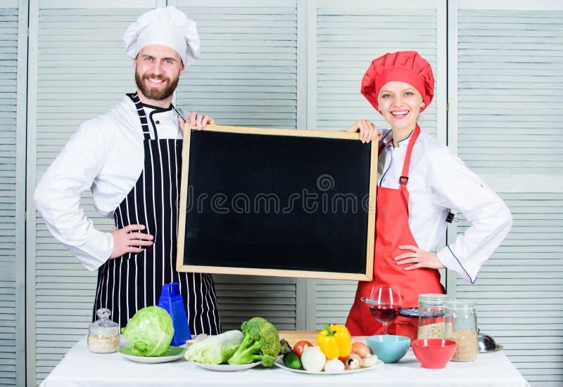 Robi? dobremu jedzeniu Szefa kuchni i kucbarskiego pomagiera nauczania mistrza klasa Para mężczyzny i kobiety mienia pusty blackb obrazy royalty free