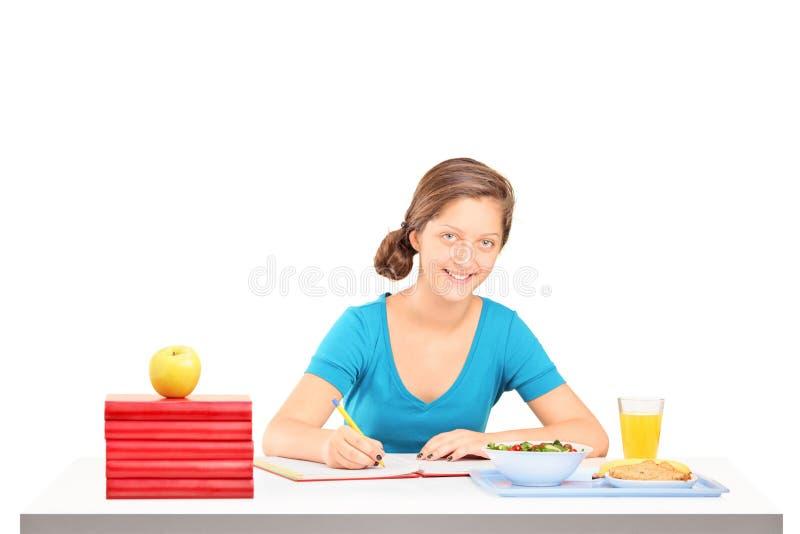 Robi jej pracie domowej uśmiechnięta uczennica zdjęcia royalty free