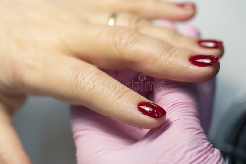 Robi manicure'owi, stosuje czerwonego gwoździa połysk na gwoździach palce w górę zdjęcie royalty free