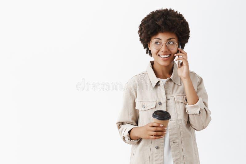 Robi? przygotowaniom przez smartphone Portret gadatliwy ?yczliwy i atrakcyjny ciemnosk?ry kobieta model w szk?ach zdjęcie royalty free