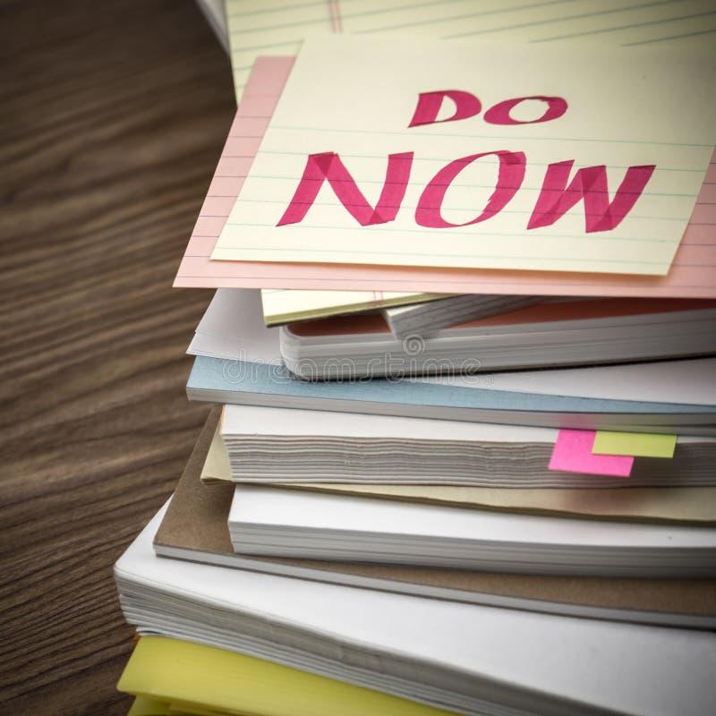 Robi Teraz; Stos Biznesowi dokumenty na biurku zdjęcia stock