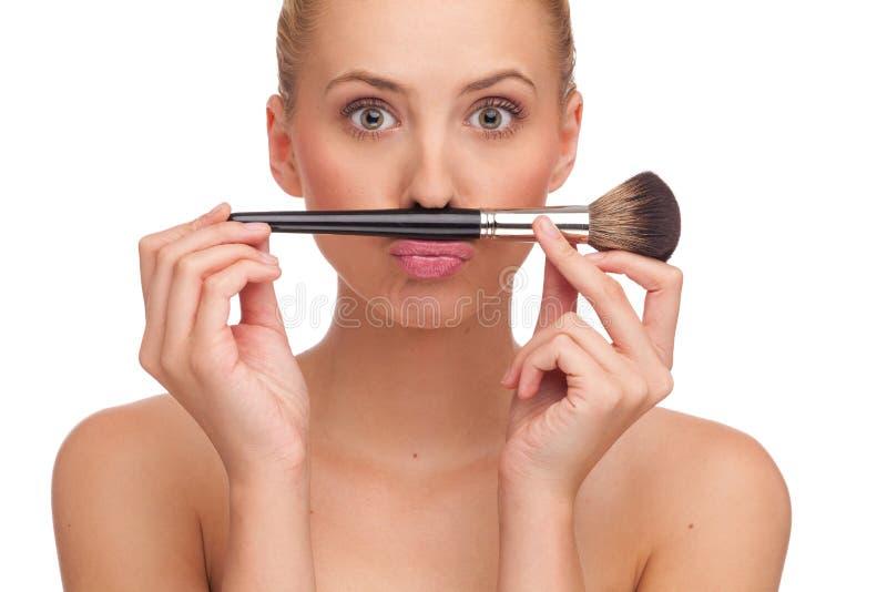 Robi wąsy z makeup szczotkować. fotografia royalty free