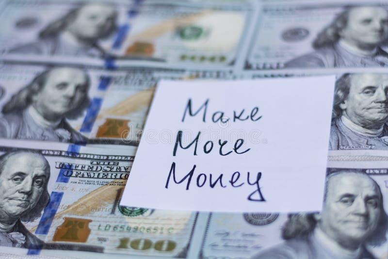Robi więcej pieniądze notatce na dolarowych rachunków tle fotografia royalty free
