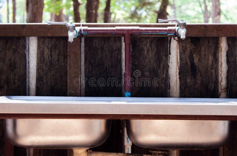 Robinet avec la baisse de l'eau dans l'évier d'acier inoxydable sur le fond de nature au concept de l'eau d'économies de forêt de photo libre de droits