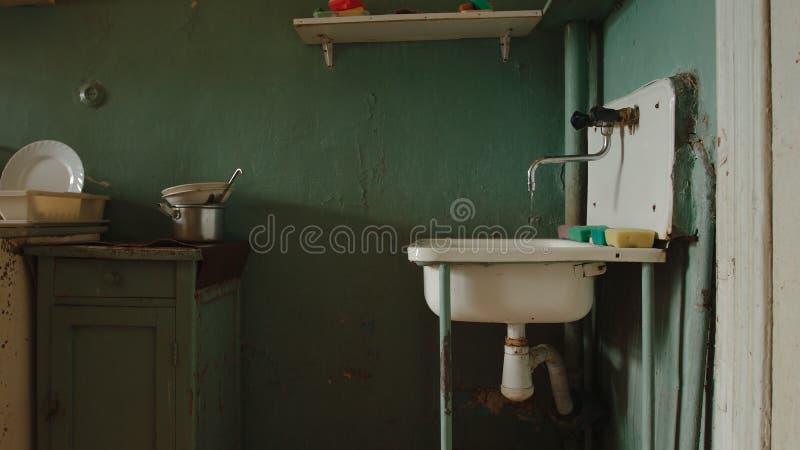 Robinet d'égoutture dans une vieille cuisine d'un appartement communal photos libres de droits