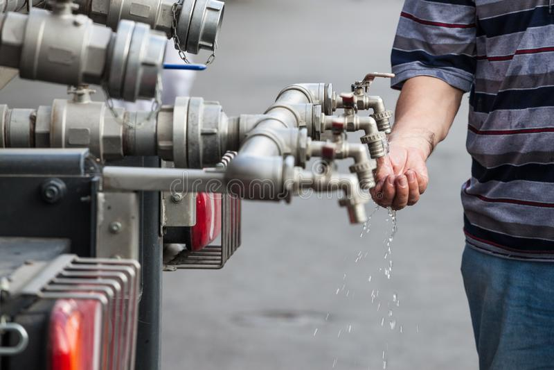 Robinet d'eau fait de plusieurs tuyaux, avec des mains essayant de tenir l'eau pour la sauver et pour la boire Ce robinet distrib photographie stock libre de droits