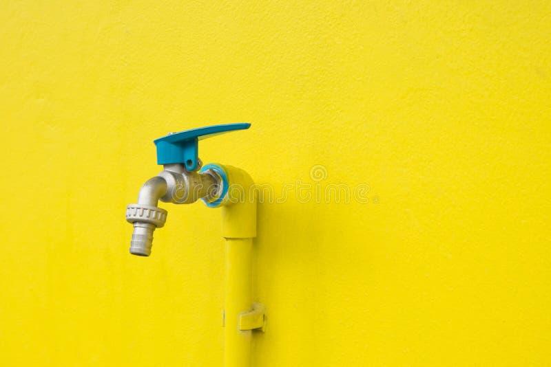 Robinet de plan rapproché sur le fond jaune concret de mur Fuite de l'eau photos stock