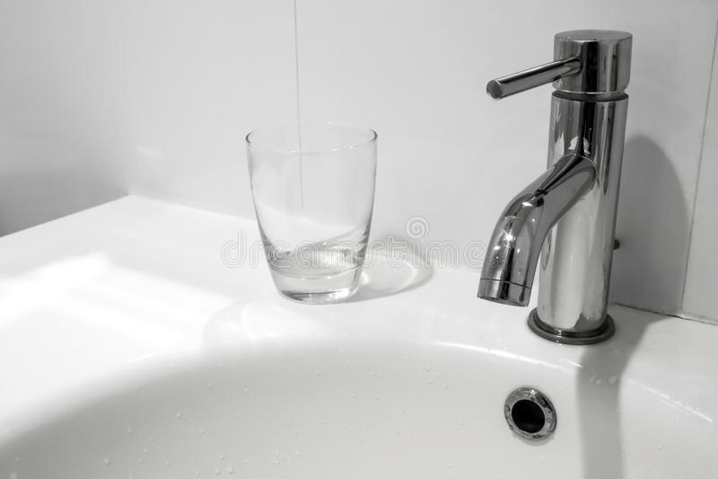 Robinet de salle de bains et lavabo avec le verre d'eau images libres de droits
