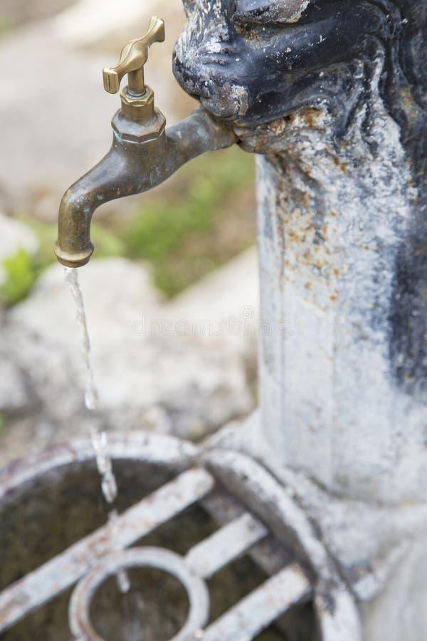 Robinet rouillé de vieux fer ouvert, avec l'écoulement de l'eau photo stock