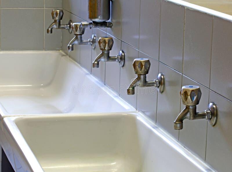 Robinets dans l'évier en céramique d'une salle de bains de l'école photos stock
